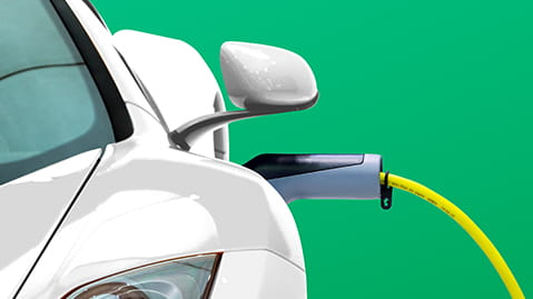 White electric car plugged into power socket with green backdrop.