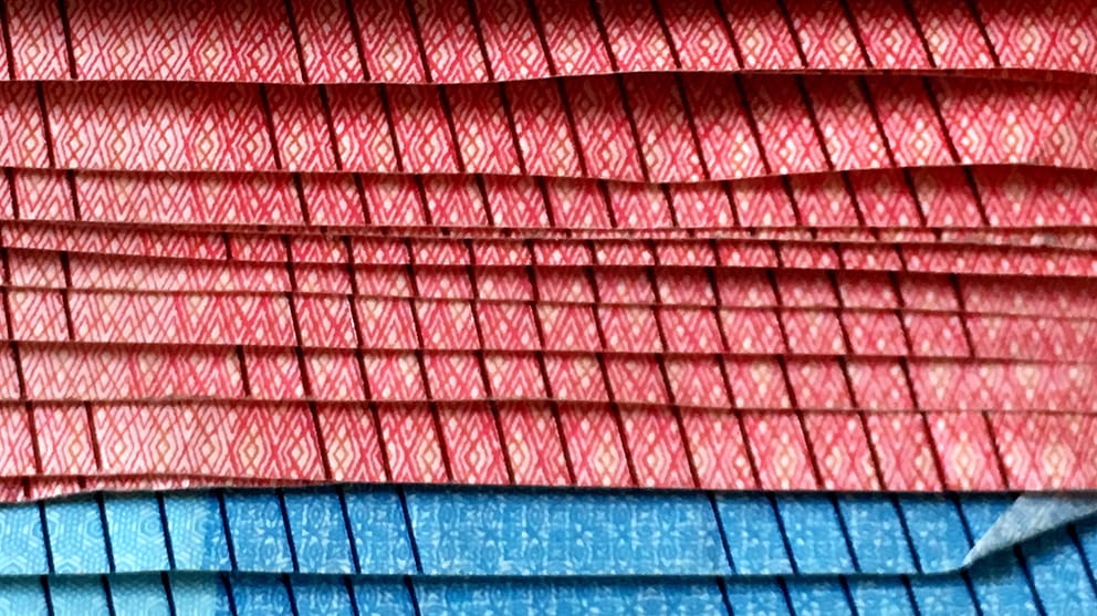 Close up of the edge of a stack of red and blue Euro bank notes