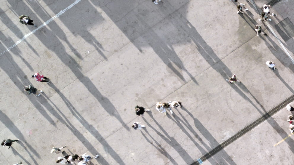 Aerial view of people walking across a concrete floor casting shadows