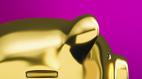 Close up of gold piggy bank in front of pink background