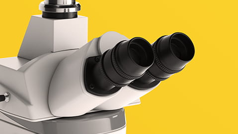 Close up of white microscope on a yellow background
