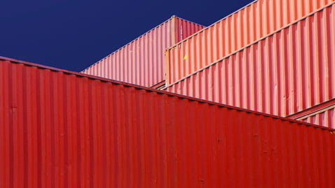 Close up of stacked red cargo containers against a blue background
