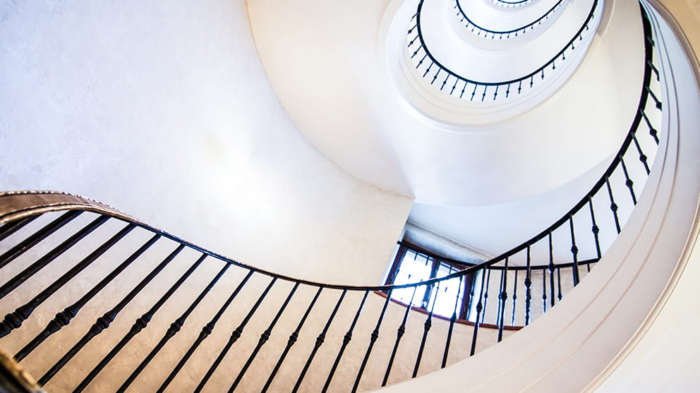 View up a spiral staircase with white walls and black railings