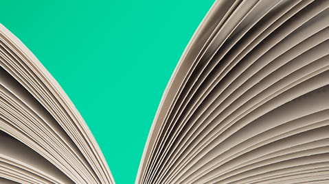 Close up of an open book against a turquoise background