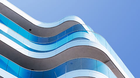 Modern building with blue glass and curving balcony.