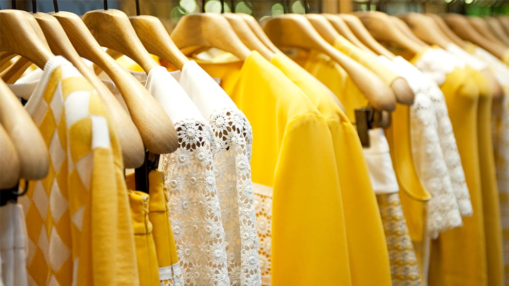 Rack of yellow and white clothes on hangers