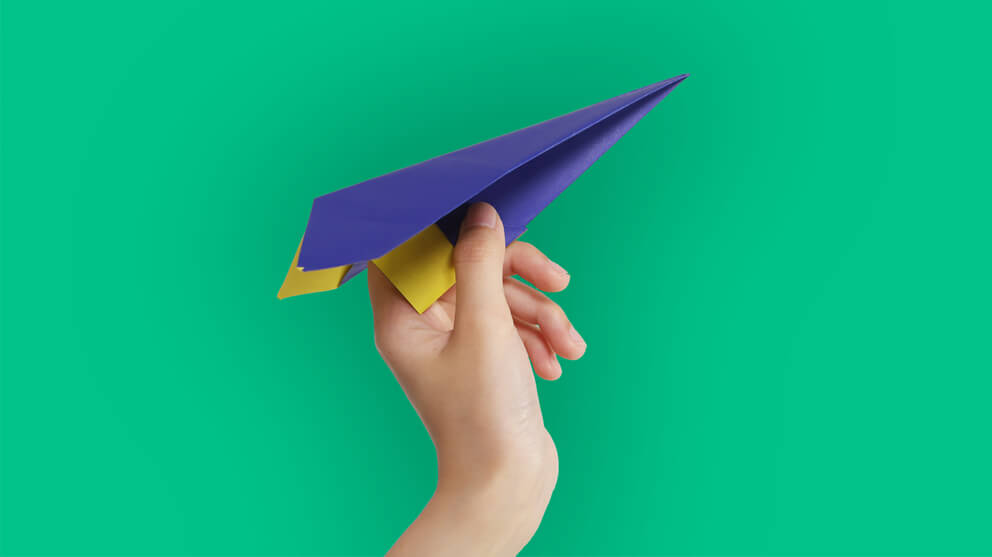 hand holding blue paper airplane