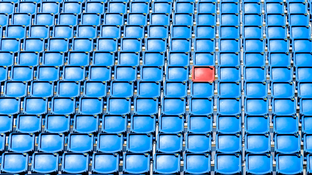 Empty red chair in middle of blue chairs