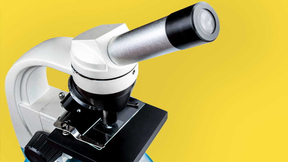 White microscope on yellow background