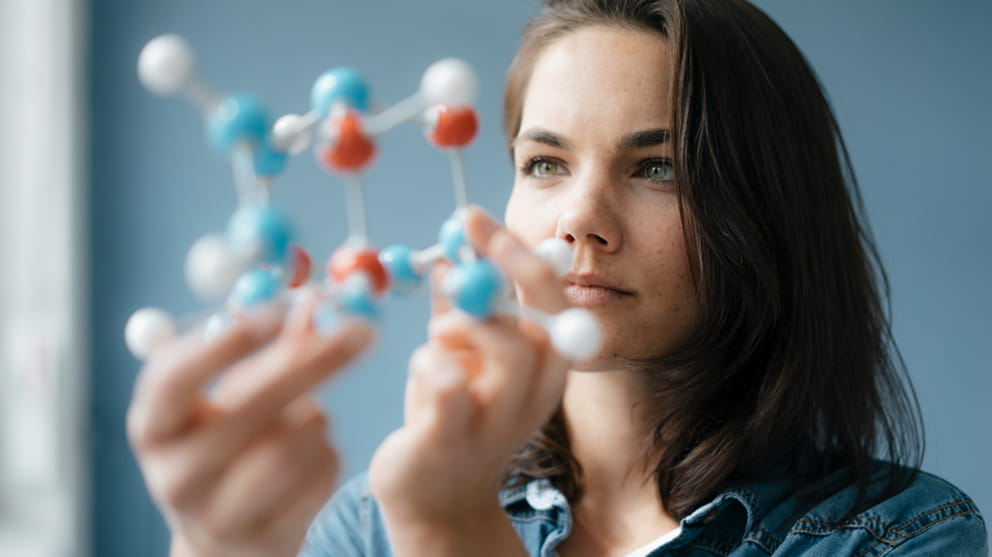 Scientist studying molecule model