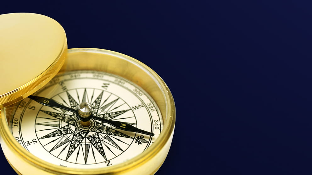 Gold coloured compass on navy blue background
