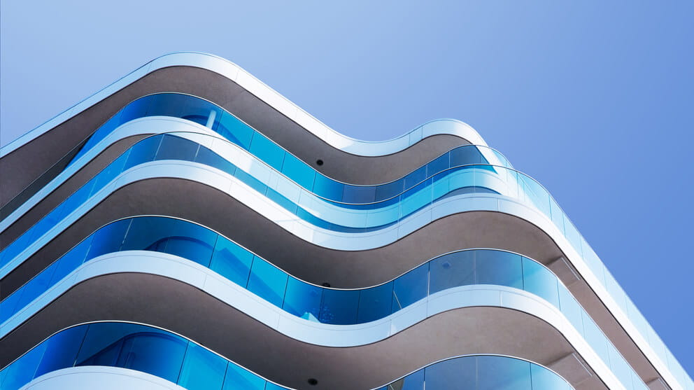 Building facade with glass balconies on blue background