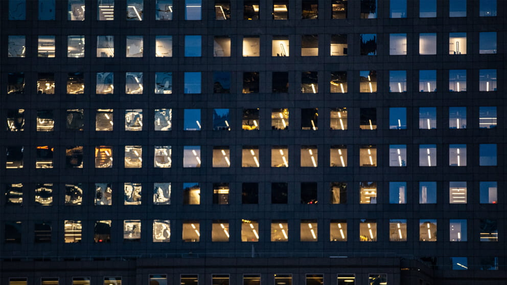Close up of office windows at night with some office lights on