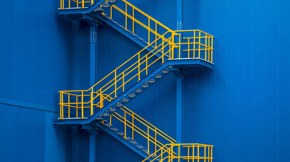 Yellow metal staircase against blue wall