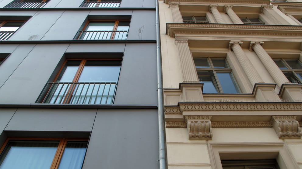 Contrast between modern and ornate old facade residential building