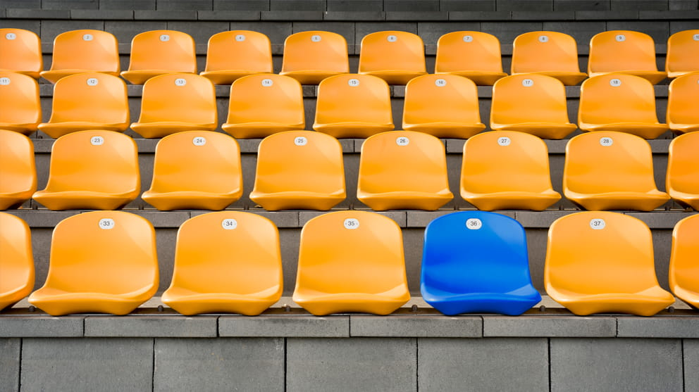 Empty blue seat in the middle of yellow seats