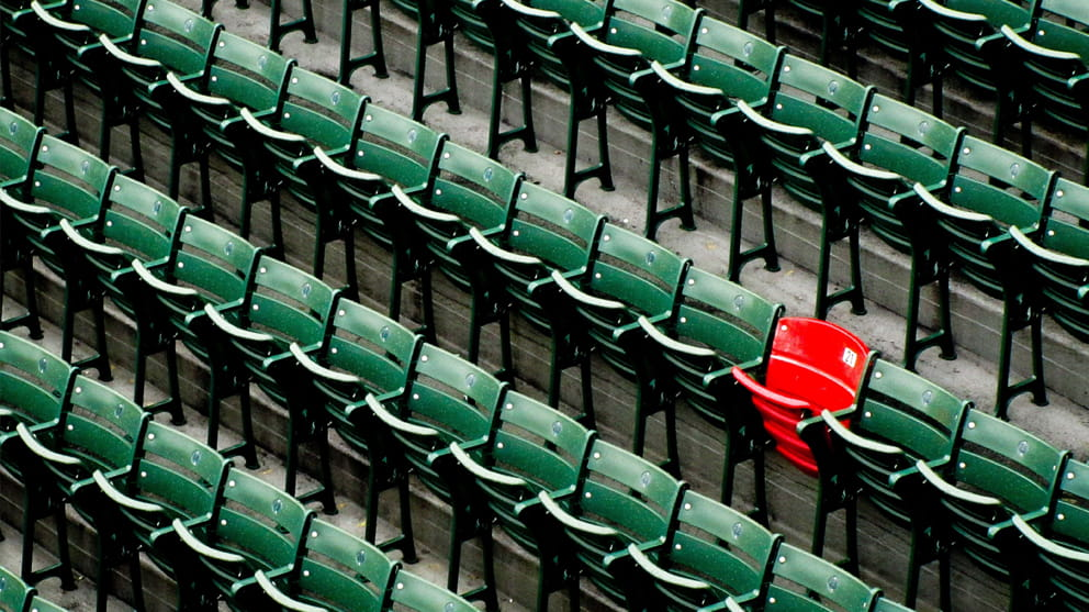 Empty red chair in row of green chairs
