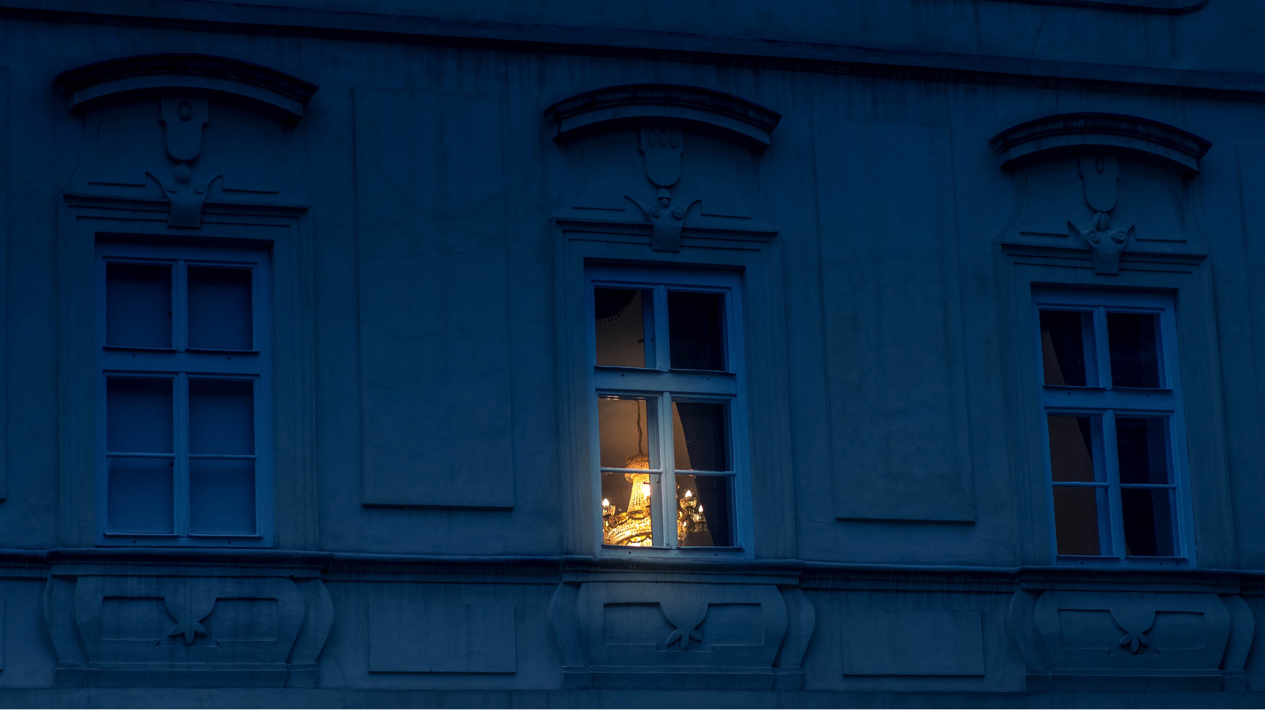 A photo of a window at night with a light shining through the window.